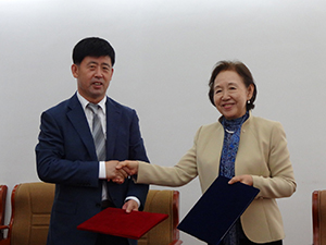 Chancellor Mizuta and President Yang shake hands following the agreement signing