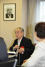 Dr. Kobayashi sits below a portrait of Mikio Mizuta before his lecture