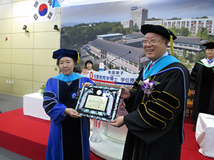 Chancellor Mizuta receives her honorary doctorate (with President Kim, left)